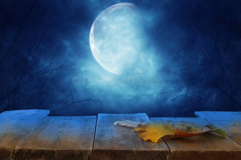 Halloween holiday concept. Empty rustic table in front of scary and misty night sky with full moon background. Ready for product d stock photography