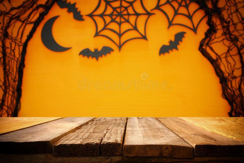 Halloween holiday concept. Empty rustic table in front of spider web and bats background. Halloween holiday concept. Empty rustic table in front of spider web royalty free stock images