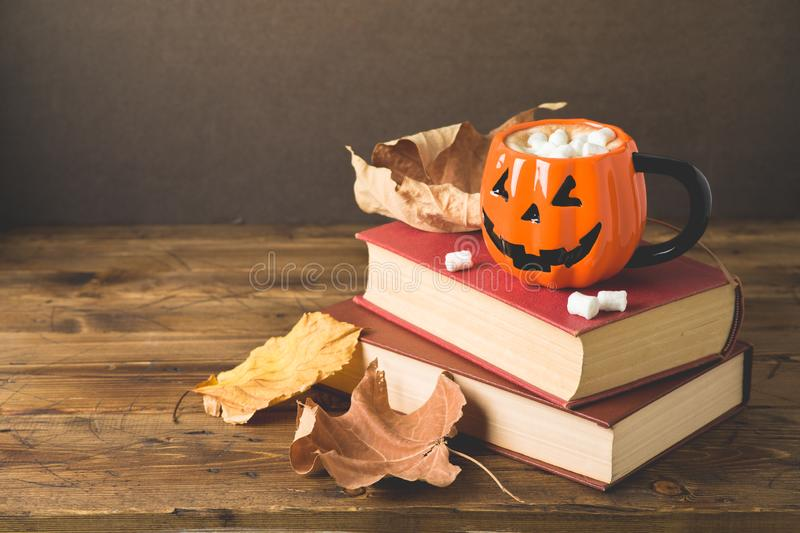 Halloween holiday concept with hot chocolate cup, books and autumn leaves stock photography