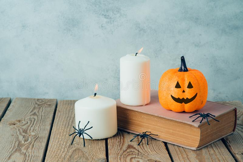 Halloween holiday concept with  jack o lantern glitter pumpkin decor, old book and candles on wooden table. Halloween holiday  concept with  jack o lantern royalty free stock photos