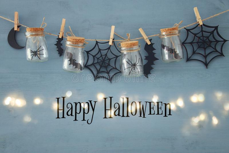 Halloween holiday concept. Masson jars with spiders, baths and wooden decorations royalty free stock photos