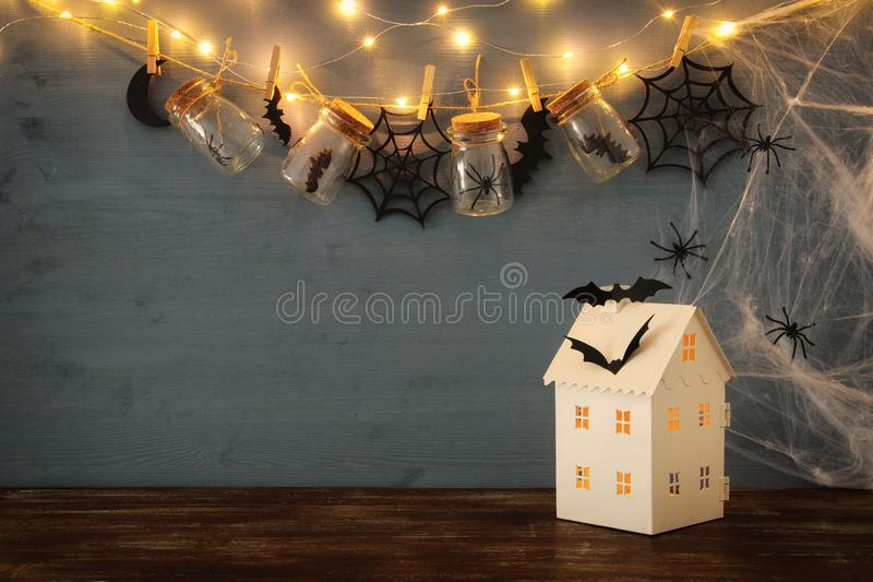 Halloween holiday concept. Mysterious house with lights in front of masson jars with spiders, baths stock photos