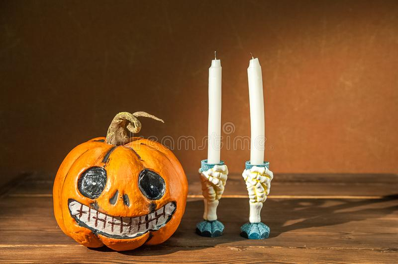 Halloween holiday concept. Pumpkin with a face. Burning and extinguished candles. Background for text with pumpkin and smoke. Hall. Oween pumpkin head jack royalty free stock photography