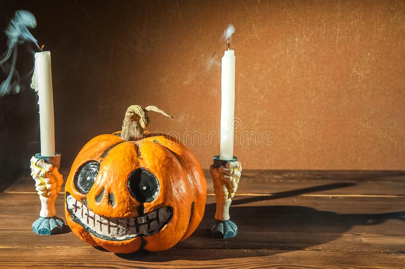 Halloween holiday concept. Pumpkin with a face. Burning and extinguished candles. Background for text with pumpkin and smoke. Hall. Oween pumpkin head jack royalty free stock photos