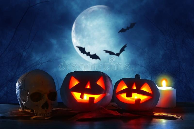 Halloween holiday concept. Pumpkins over wooden table at night scary, haunted and misty forest. royalty free stock photo