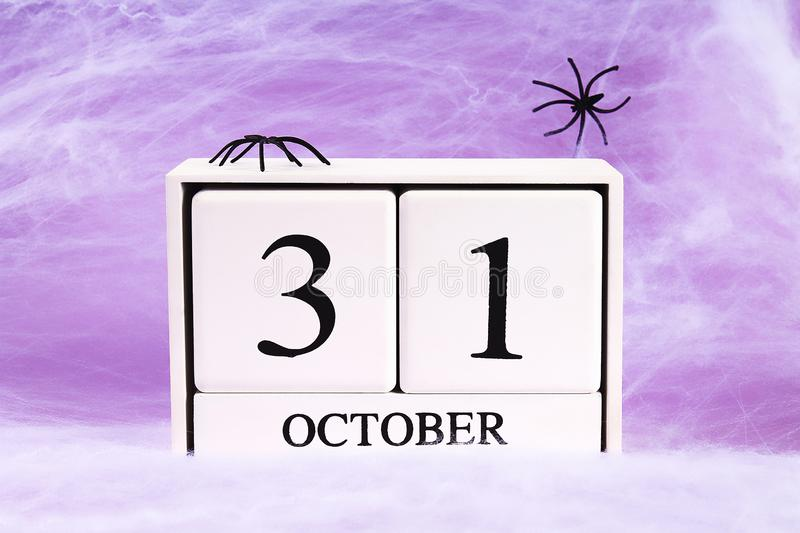 Halloween holiday concept. White spider web with two black spider web purple background. October 31 royalty free stock photo