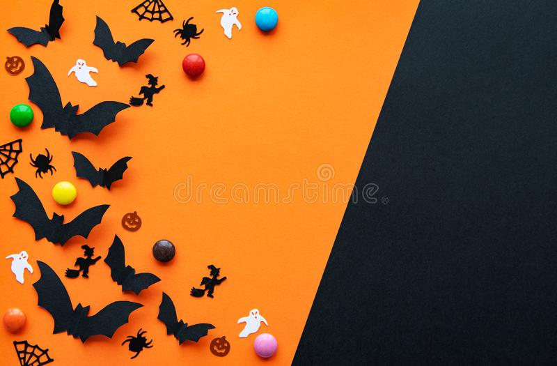 Halloween holiday decorations. Halloween  concept - black paper bats and decorations flying over orange background stock photo