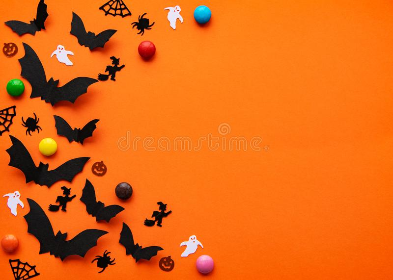 Halloween holiday decorations. Halloween  concept - black paper bats and decorations flying over orange background stock photos