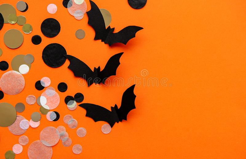Halloween holiday decorations. Paper bats and confetti  on orange  background. Flat lay, top view royalty free stock photo