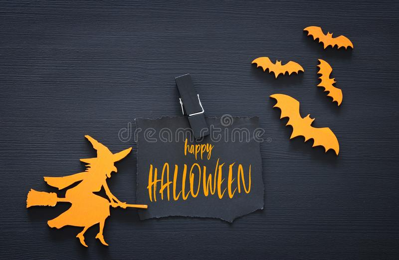 Halloween holiday minimal top view image of letter with text HAPPY HALLOWEEN over wooden black background. Card and invitation con royalty free stock photos