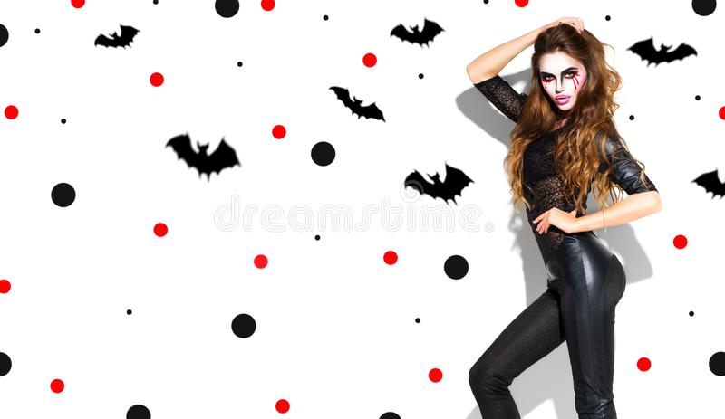 Halloween. Holiday party girl. Beautiful young woman with bright vampire makeup and long hair posing in witches costume. Halloween. Holiday party girl makeup stock images
