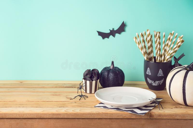Halloween holiday table setting with glitter black pumpkin, party chalkboard cup and candy. Halloween holiday table setting with glitter black pumpkin, party stock image