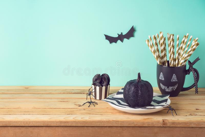Halloween holiday table setting with glitter black pumpkin, party chalkboard cup and candy. Halloween holiday table setting with glitter black pumpkin, party stock photography