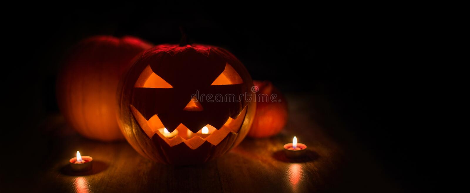 Halloween jack-o-lantern burning in darkness. Halloween and holidays concept - spooky carved pumpkin jack-o-lantern with candles in darkness royalty free stock photo