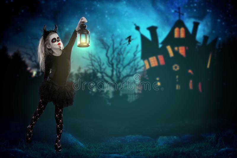 Halloween, holidays, masquerade concept - the portrait of young little beautiful girl with skull makeup holding a lamp. Halloween,. Face-art, skull make up stock photography