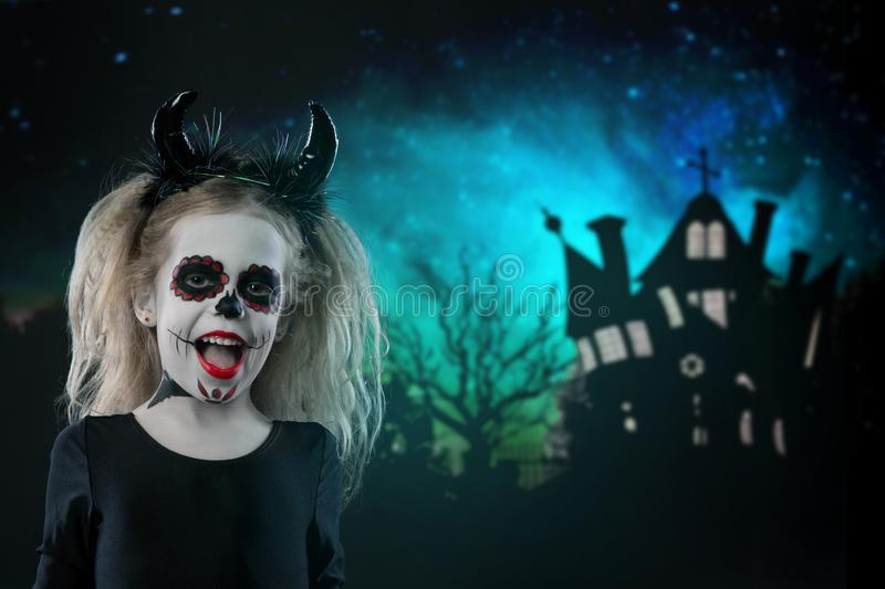 Halloween, holidays, masquerade concept - the portrait of young little beautiful girl with skull makeup and horns. Halloween, face. Art, skull make up concept royalty free stock photo