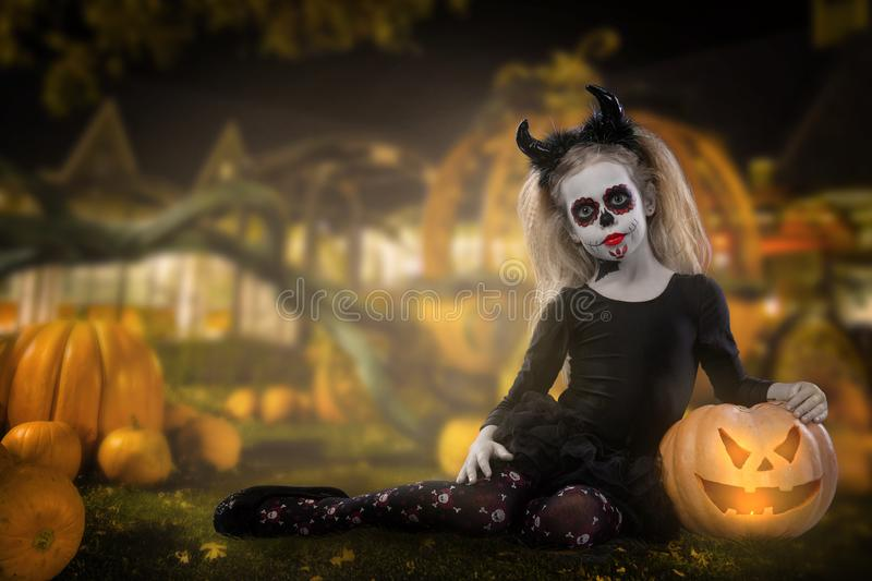 Halloween, holidays, masquerade concept - the portrait of young little beautiful girl with skull makeup on pumpkins background. Ha. Lloween, face-art, skull make stock photography
