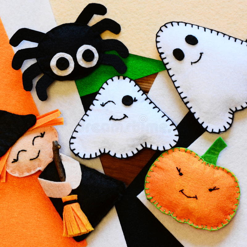 Halloween home decor toys. Felt witch with broom, pumpkin head, two ghosts, spider. Halloween crafts on colored felt sheets stock photography