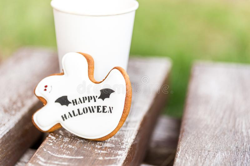 Halloween homemade gingerbread and honey cookies  as a white ghost with happy halloween greetings text on a wooden bench and cup royalty free stock photo