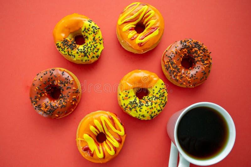 Halloween i jesień barwiliśmy smakowitych kolorowych donuts słuzyć dla śniadania na kuchennym stole z dudkowaniem - gorąca kawa zdjęcie stock