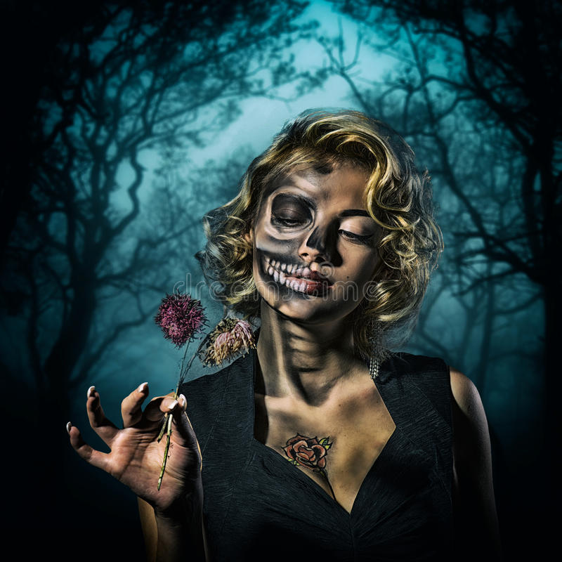 Halloween image – female portrait. Portrait of a retro woman with skull make-up and dried flowers in her hand in the night forest royalty free stock photography