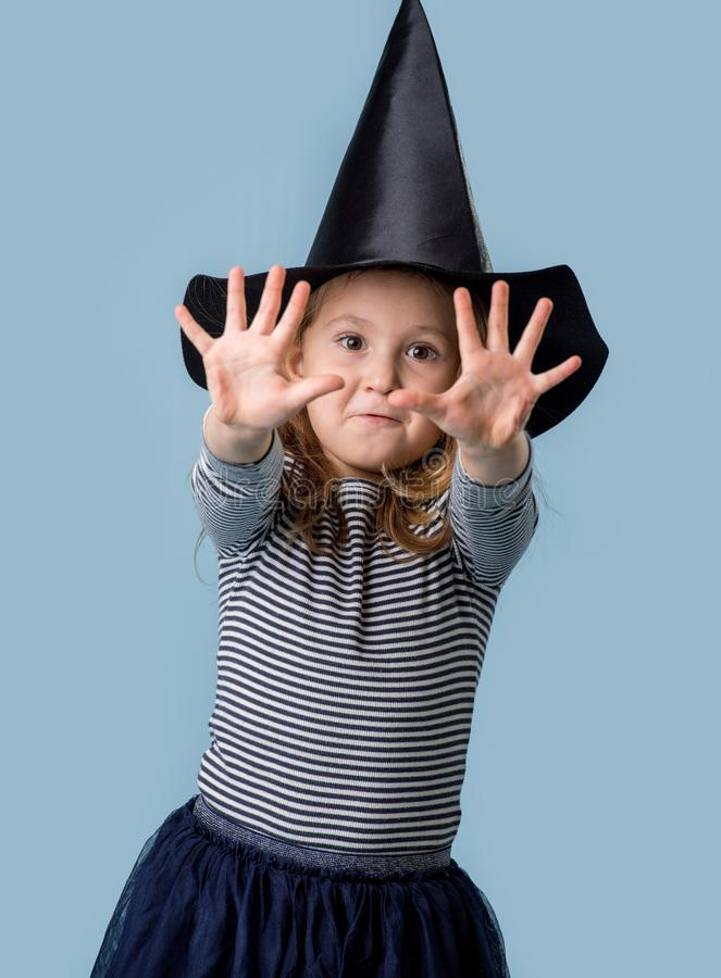 Portrait of a girl in a witch costume, pulls hands and shows fingers stock photo