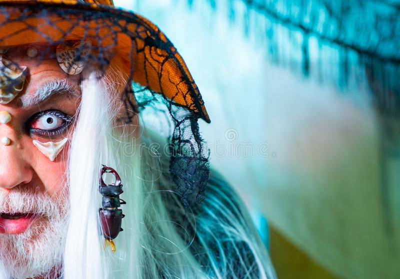 Halloween insect, bug on Face. Halloween man. Halloween demon. Demon with skull on Halloween party. stock photos
