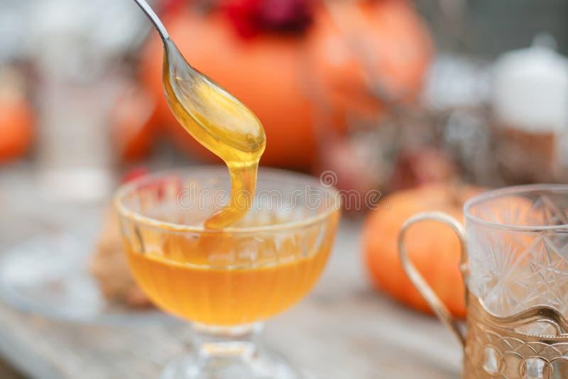 Halloween-Inspiration Holztabelle des Kuchens n Des Herbstes Leben noch Kürbis, trockene Rosen, Viburnumhonig in einem Vase twigs stockfotografie