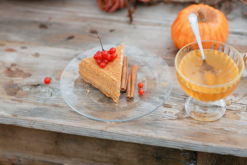 Halloween-Inspiration Holztabelle des Kuchens n Des Herbstes Leben noch Kürbis, trockene Rosen, Viburnumhonig in einem Vase twigs stockfotos