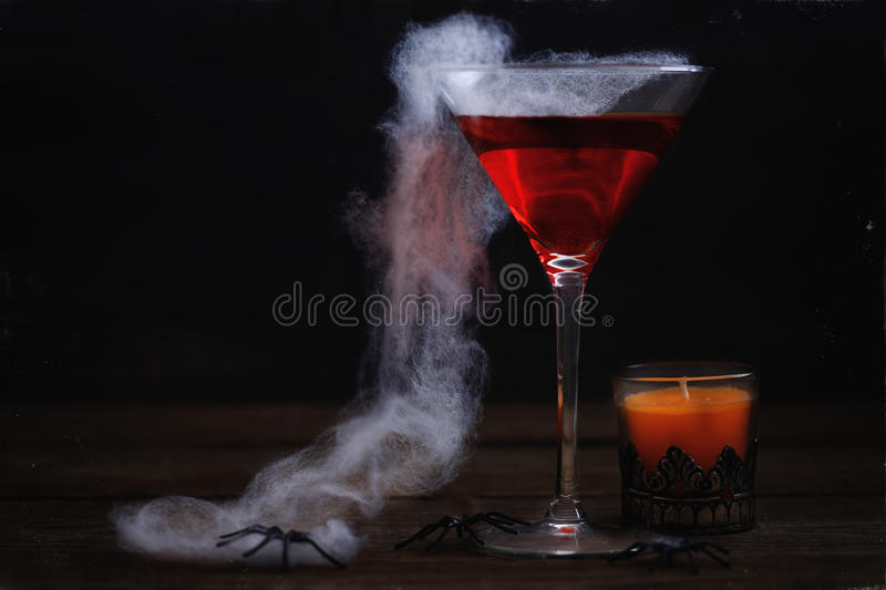 Halloween items over rustic wooden background. Spooky Halloween drink, spider web and orange candle over rustic wooden background. Aging effect, colour toning royalty free stock image