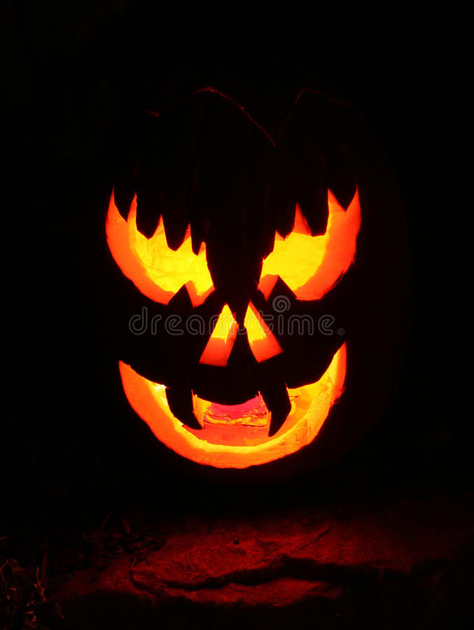 Halloween jack-o-lantern. Scary glowing face of halloween jackolantern in the dark stock image