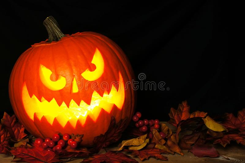 Halloween Jack o Lantern with autumn leaves on black background. Spooky Halloween Jack o Lantern with autumn leaves on a black background royalty free stock photography