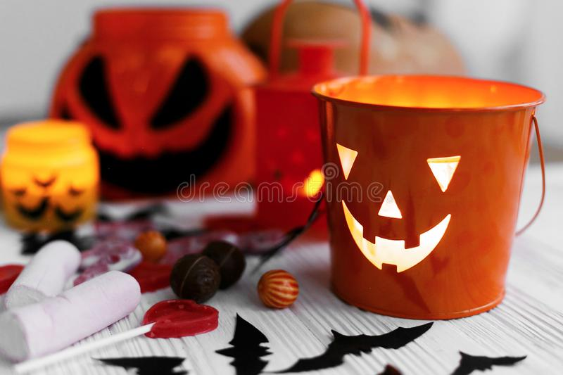 Halloween jack o lantern bucket, glowing candle, festive candy, skulls, black bats, ghost, spider decorations on white wooden. Background. Copy space. Trick or stock image