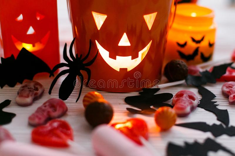 Halloween jack o lantern bucket, glowing candle, festive candy, skulls, black bats, ghost, spider decorations on white wooden. Background. Copy space. Trick or stock photos