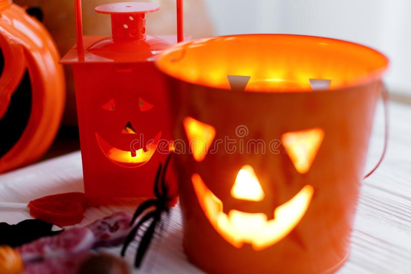 Halloween jack o lantern bucket, glowing candle, festive candy, skulls, black bats, ghost, spider decorations on white wooden. Background. Copy space. Trick or royalty free stock photo