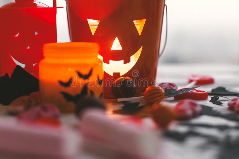 Halloween jack o lantern bucket, glowing candle, festive candy, skulls, black bats, ghost, spider decorations on white wooden. Background. Copy space. Trick or royalty free stock photography