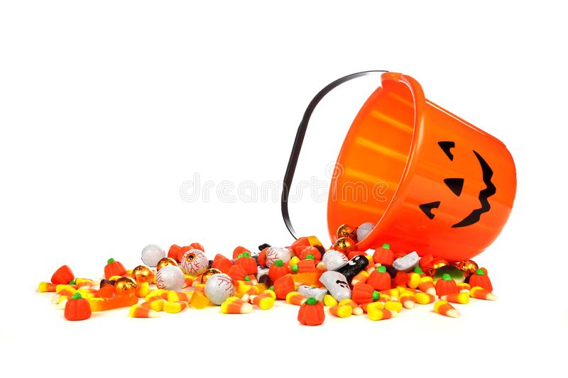 Halloween Jack o Lantern candy collector with spilling candy over white royalty free stock photography