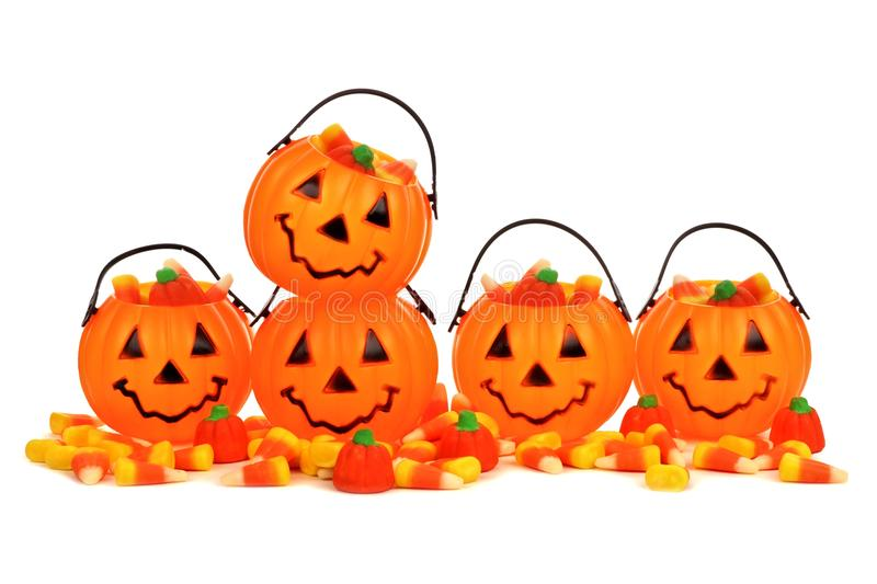 Halloween Jack o Lantern candy holders with scattered candy stock photo
