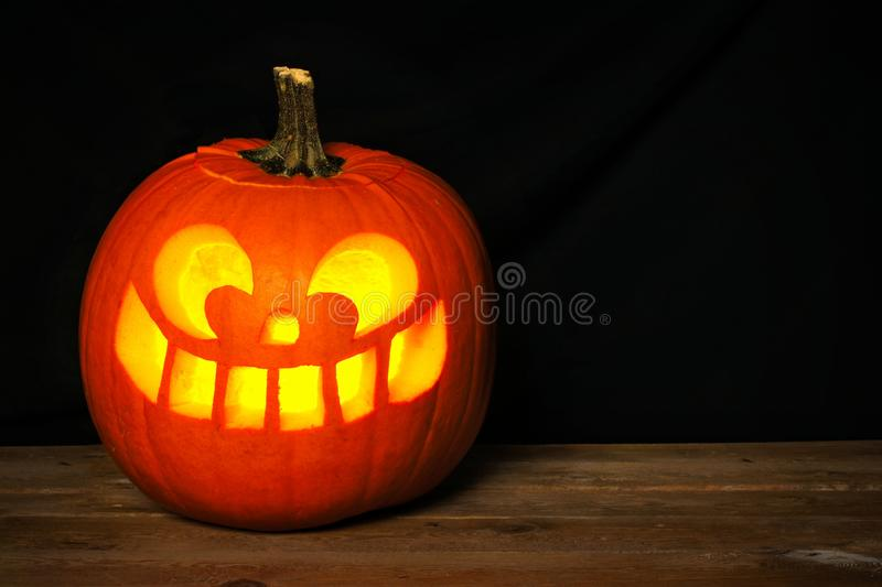 Halloween Jack o Lantern on old wood with black background. Single spooky Halloween Jack o Lantern on old wood with a black background royalty free stock images