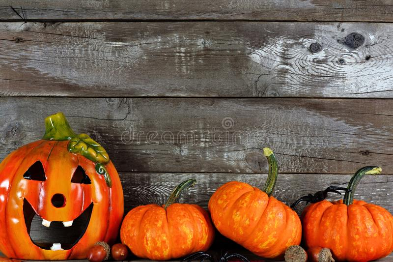 Halloween Jack o Lantern with pumpkin bottom border against wood royalty free stock photo