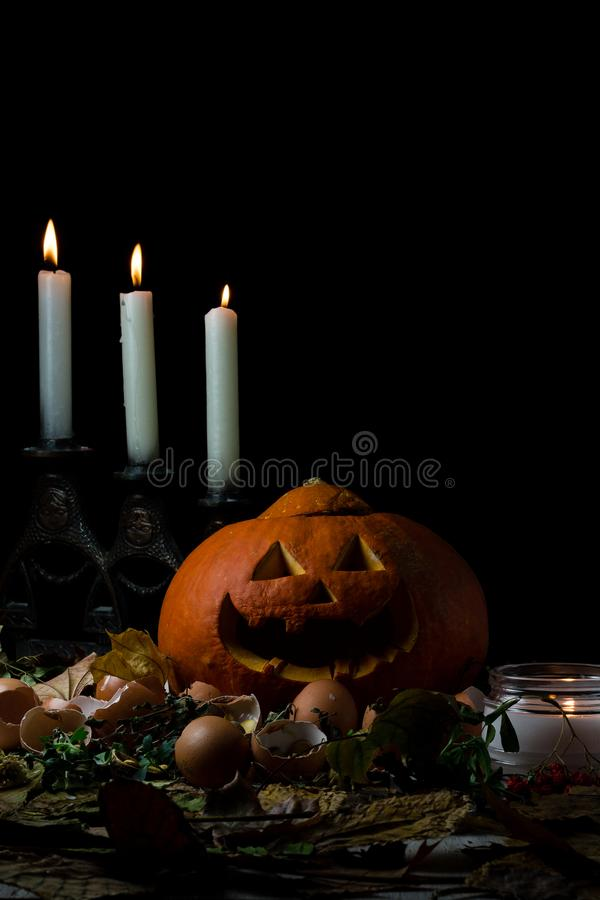 Halloween jack-o-lantern pumpkin and candles on autumn leaves royalty free stock images