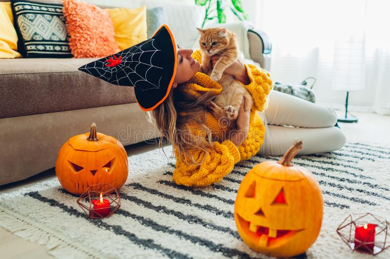 Halloween jack-o-lantern pumpkins. Woman in hat playing with cat lying on carpet decorated with pumpkins and candles royalty free stock images