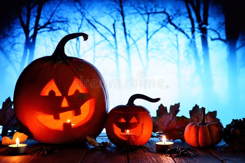 Halloween Jack o Lanterns against spooky blue lit forest. Halloween Jack o Lanterns. Night scene with a blue spooky forest background stock image