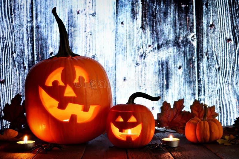 Halloween Jack o Lanterns, night scene against wood stock image