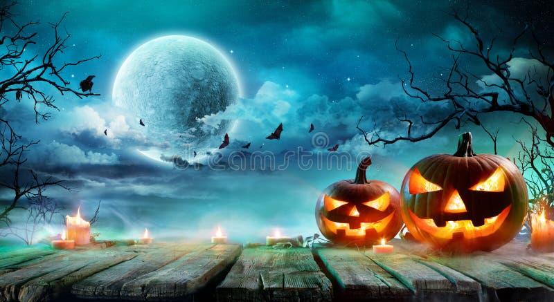 Halloween- - Jack-O ` Laternen und Kerzen auf Tabelle stockbilder