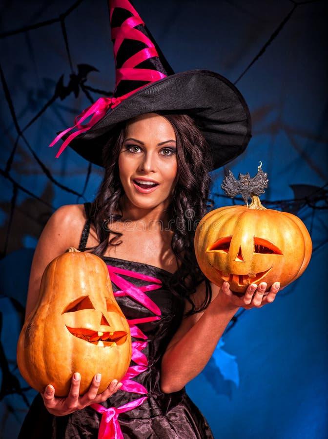Halloween-Kürbis in den Hexenfrauenhänden stockbild