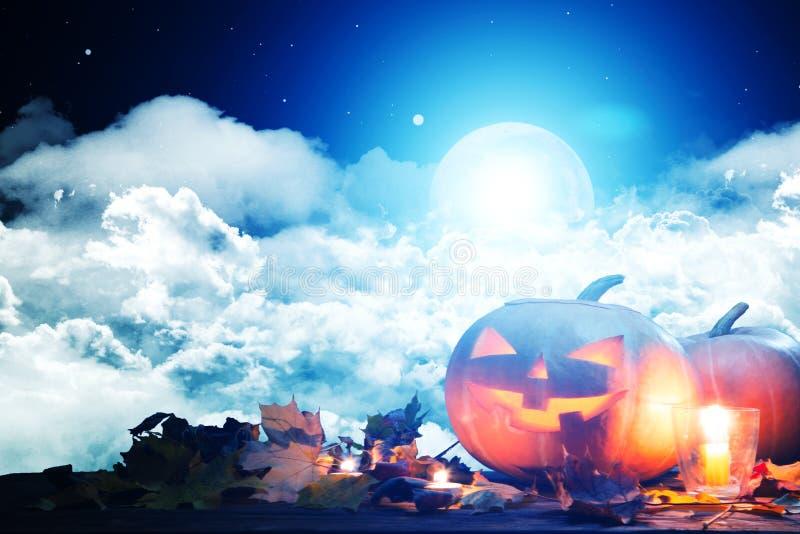 Halloween-Kürbis Jack--O` - Laterne auf Holztisch mit Kerzen in einer gespenstischen Nacht über Mond und Wolken lizenzfreie stockbilder