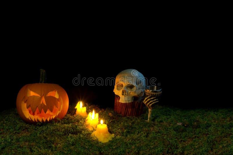 Halloween-Kürbis, menschlicher Schädel, Becher und Kerzen, die in Th glühen stockbilder