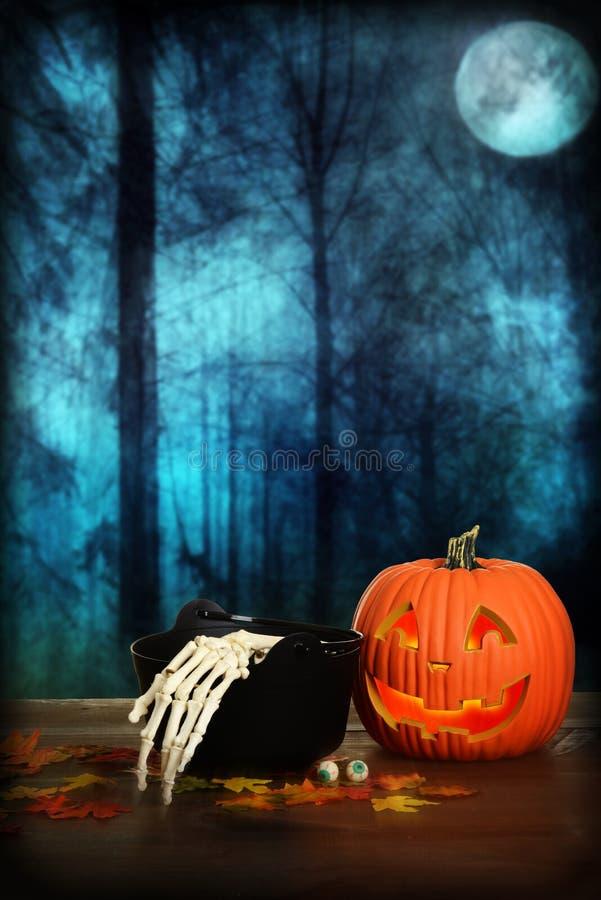 Halloween-Kürbis mit der Skeletthand und großem Kessel lizenzfreies stockbild