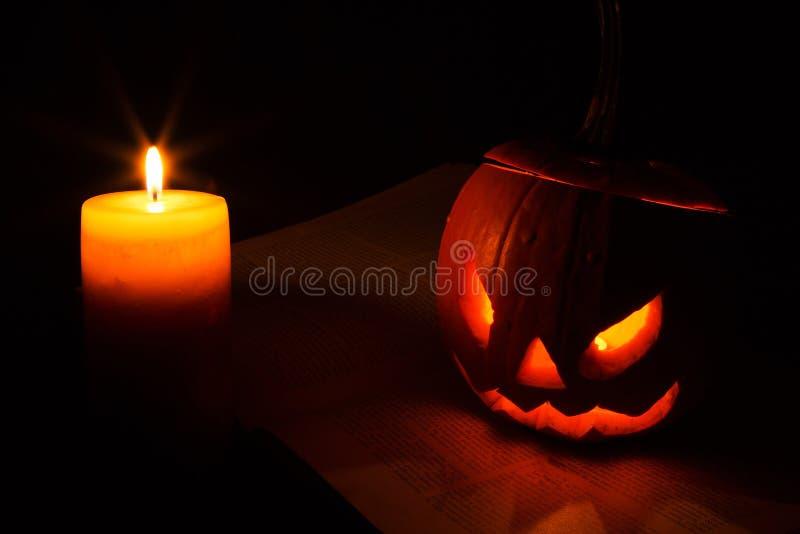 Halloween-Kürbis und -kerze auf dem Buch stockfotos